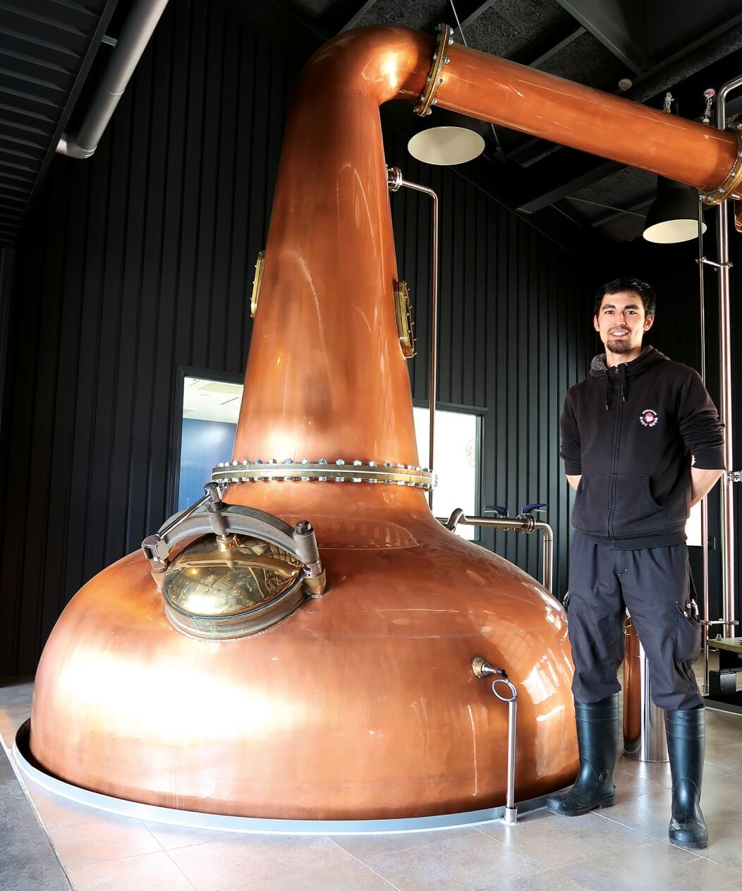Head distiller Sam Yoneda next to the wash still