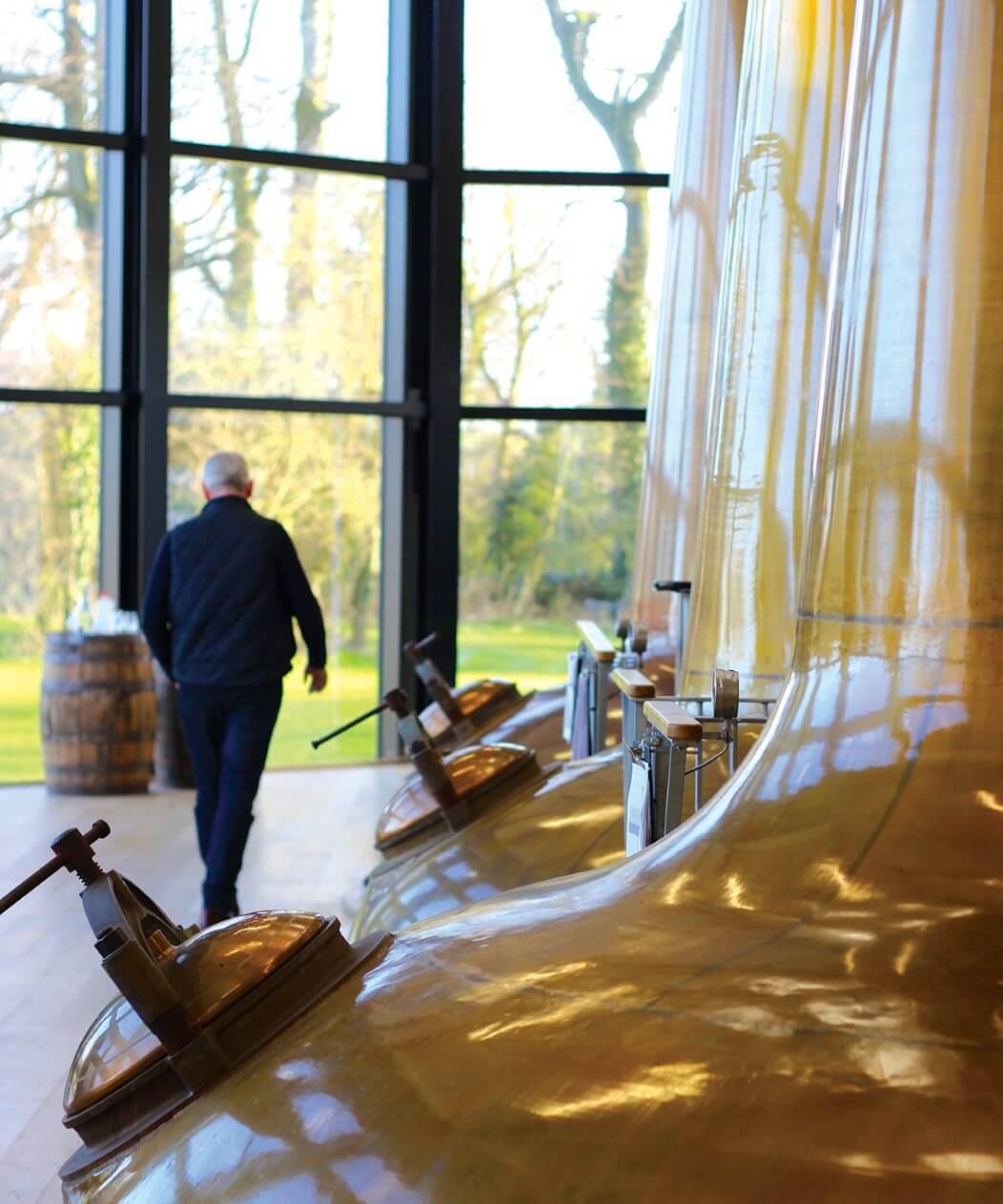 Bernard Walsh walks across his stillhouse floor